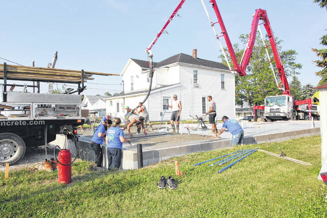 Work is continuing on the newest Habitat for Humanity house which is being built in Sidney at 524 Second Ave. The foundation for the house was being poured Monday Woehrmyer Concrete as Brian Miller, of St. Marys, guides the pump and hose with the concrete. Emerson Climate Technologies employees Tammi Miller, of Sidney, Katy Zimpfer, of Botkins, and Brad Parsons, of Sidney, lend a hand during the process. Emerson and Cargill are the the corporate sponsor of the project. The house is being built for Kelly Beemer and her children.