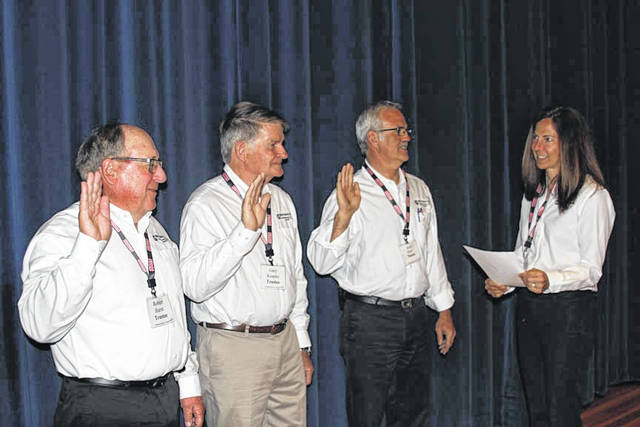 Incumbent Midwest Electric Inc. trustees Robert Barnt, left to right, Gary Knapke and Roger Rank are sworn into office by Courtney Burton during the cooperative's annual meeting, Saturday, June 2, in St. Marys.