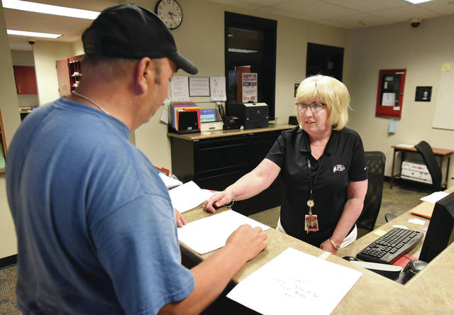 Fort Loramie Elementary Secretary Julie Moeller, right, talks with maintenance worker Dave Goldschmidt, both of Fort Loramie, about how to disarm the school's security alarm Tuesday, June 12.