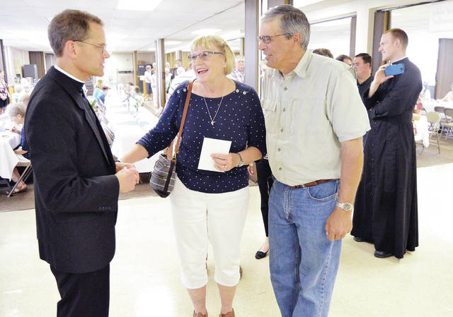 The Rev. Patrick Sloneker, left to right, talks with Peg and Jim Buehler, all of Botkins, as the Rev. Sean Wilson, of Fryburg, waits to take a photo of Sloneker at Immaculate Conception Catholic Church in Botkins Sunday, June 24.