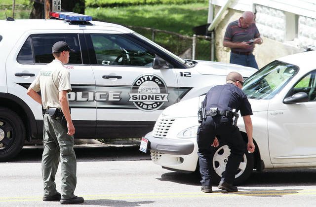 Sidney Park Ranger Justin Aselage, left, and a Sidney Police officer look at a PT Cruiser after it struck a child in the 300 block of Riverside Drive, Thursday, June 27. The crash remains under investigation.
