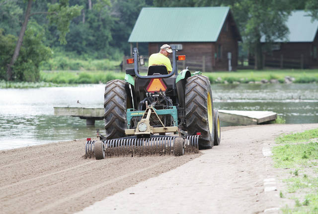 John Kaiser, of Coldwater, rakes the beach at Lake Loramie State Park Wednesday, June 27. Raking the beach breaks up sand that has hardened making it softer for beachgoers. As temperatures continue to rise the beach will become a more popular hang out.