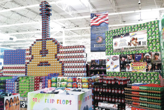 """The annual Country Concert Walmart display is now up. The display consists of a guitar and U.S. flag made of pop boxes. Also designed with pop boxes is the silhouette of a person saluting over the U.S. flag with the word """"Welcome"""" underneath. Being sold in front of the display are things commonly seen at Country Concert such as folding lawn chairs, flip flops and coolers. Country Concert will be held July 5-7 in Fort Loramie."""