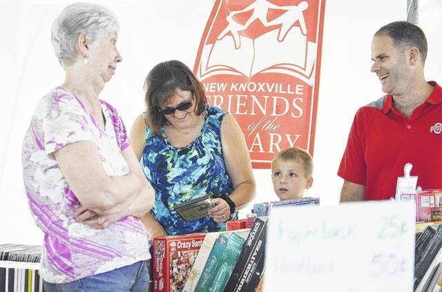 Volunteer Terry Luedeke, left to right, of Wapakoneta, talks with Amy Steinke, her son Gabe Steinke, and Gabe's dad Craig Steinke, all of New Knoxville, as the Steinke's browsed the books on sale by the group New Knoxville Friends of the Library during the 2017 New Knoxville Independence Day.