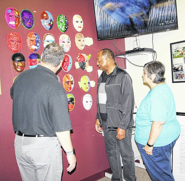 Brad Reed, left, of Troy, with Tri-County Board of Recovery and Mental Health Services, Alphonso Darden, of Sandusky, with Sandusky Artisans Recovery Community Center, and Teresa Bown, of Botkins, with SafeHaven in Sidney, look over an exhibit of masks made by SafeHaven clients, recently. The exhibit was on display during SafeHaven's open house.