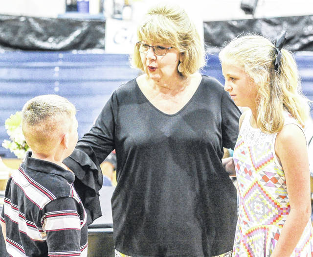 Christian Academy Schools Superintendent Mary Smith, center, of Sidney, talks with students during a reception in honor of her retirement, Sunday, June 3, at the school in Sidney. Levi Thompson, 7, left and Mackensie Douglas, 10, are the children of Brittany and Justin Thompson, of Sidney.