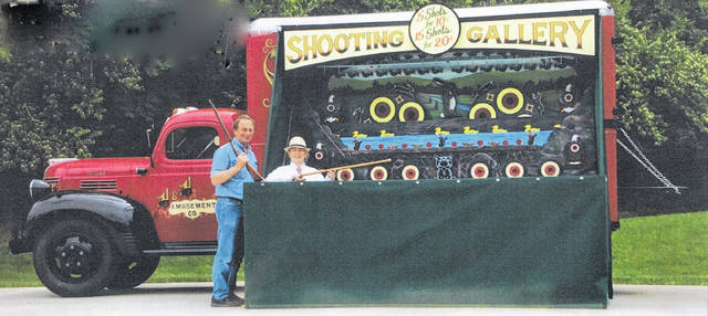 Ron, left, and Jan Helman, of Sidney, with their 1914 carnival shooting gallery. They will display it in Tawawa Park during the 70th anniversary celebration of the park, June 30.