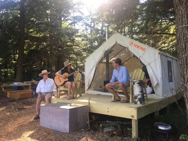 In this Friday, June 29, 2018, photo, Michael D'Agostino, right, sits with Robert and Sally McCracken at their Tentrr campsite in Sand Lake, N.Y. D'Agostino, CEO of Tentrr, says it's like Airbnb or Uber for the great outdoors, providing a platform for landowners to earn some cash by sharing secluded and scenic sites for camping. (AP Photo/Mary Esch)
