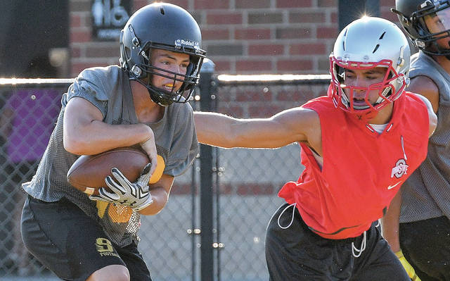 Sidney junior defensive back Clay Carter comes down with an interception with pressure from a Lima Senior wide receiver during a 7-on-7 passing camp on Wednesday at Sidney Memorial Stadium. Defensive backs are among Sidney's deepest units.