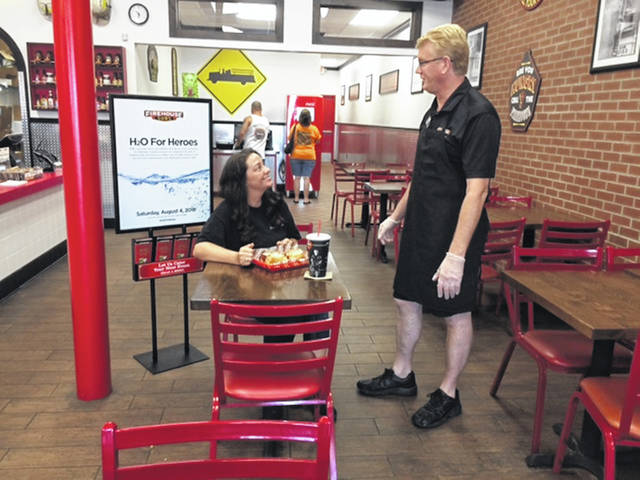Tom Martin, right, owner of the Firehouse Subs franchise in Sidney, tells Jessalyn Younce, of Troy, about the H2O for Heroes project as he serves her a sandwich, Friday, July 27.