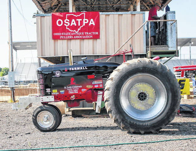 A 1941 Farmall M, top photo, is being raffled in a 50/50 raffle across multiple states. The tractor was on display Sunday at the Shelby County Fairgrounds during an antique tractor pull sponsored by the Ohio State Antique Tractor Pullers Association Pull. The winning ticket will be drawn Dec. 1, 2018, in Tunica, Mississippi. Proceeds from the event will benefit St. Jude's Hospital. A group of guys got the tractor in Tunica and has stripped it, refinished it, painted so that it can be raffled to help the St. Judes Hospital. This is the sixth tractor to be raffled for St. Jude's. So far this year, $20,000 has been raised for the hospital. By the time the winning ticket is drawn, they hope to have raised $50,000. Jeff Poeppelman, of Russia, traveled to Mason, Michigan, to pick the tractor up so that it could be at the tractor pull Sunday. To purchase tickets online for the raffle, visit https://tunicaraffletractor.blogspot.com/ The Farmall will be featured in the Hook Magazine every year, Bryan Livley from the Hook magazine helps feature the tractors and to help raise the money. While the tractor was on display, the tractor pull participants were busy at the event. In the photo below, Wayne Cook drives a 1968 Farmall 1206. He was the winner of the 10mph group at 382.21.