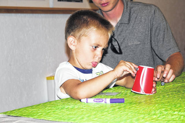 Colton Sherman, 3 , son of Angel and Brian Sherman, of Houston, adds eyes to his windsock he was making at the Fun with Nature Crafts program in the Community Foundation Hall.