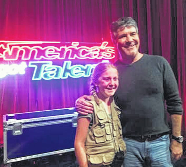 "Lilly Wilker, 11, left, gets a hug from ""America's Got Talent"" judge Simon Cowell on the set in California in April. The daughter of Amy and Tom Wilker, of New Bremen, had just taped her second appearance on the show, which will air Tuesday, July 14."