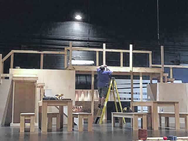 "Scenic designer Jacob Brown works on a 7-foot high bridge that is the centerpiece of the set for the Towne and Country Players' production of ""Oliver."" The musical opens in Versailles, July 19."