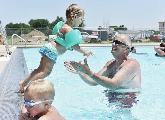 Caroline Huelskamp, 3, jumps into the arms of her grandpa Chip Wells, both of Sidney, at the Wally Byam Memorial Pool in Jackson Center Wednesday, July 11. In front is Colton Huelskamp, 5, of Sidney. Colton and Caroline are the children of Rachel and Doug Huelskamp.