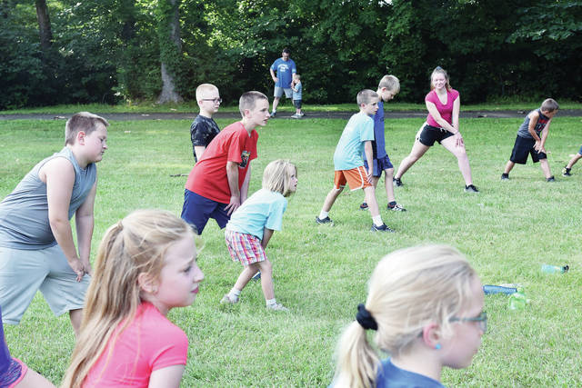 Kids stretch at the start of a kids fun fun clinic taught by Can't Stop Running Company staff at Tawawa Park Tuesday, July 10. The clinic introduces kids to running, fitness and wellness. Kids will play games, hold races and listen to guest speakers.