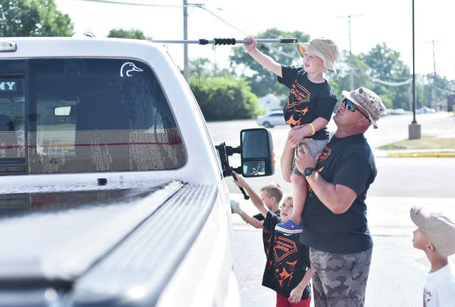 Alex Lacy, 4, of Sidney, son of Aaron and Melissa Lacy, gets a lift from Craig Pohl, of Troy, so he can reach the top of a pickup truck during a car wash at Advanced Auto Parts, Saturday, July 14. Also helping are, left to right, Alex's brother, Jameson, 7, and Liam Bosslet, 6, son of Zack and Sherri Bosslet, of Sidney, and Sullivan Pohl, 6, of Troy, son of Craig and Michelle Pohl. The car wash raised money for Alex's Relay for Life team.