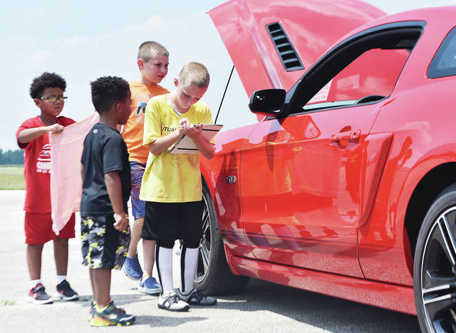 Carter McNabb, far right, 8, of Sidney, son of Trista and Josh McNabb, rates the cars taking part in the Carterfest Car, Truck and Bike Show at the Sidney Airport Saturday, July 14. With Carter are, left to right, Urijah McGhee, 7, and Xerus McGhee, 6, both the sons of Lacost'a and Conrad McGhee, and Carter Lawson, 8, all of Sidney, son of Brian Lawson and Sara Francis. Carterfest was held to raise money in Carter's fight with Cystic Fibrosis.