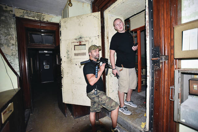 Steven Shiverdecker, left, of Lewisburg, prepares to videotape Josh Deal, of Troy, as they walk through the old Sidney jail Saturday, July 14.