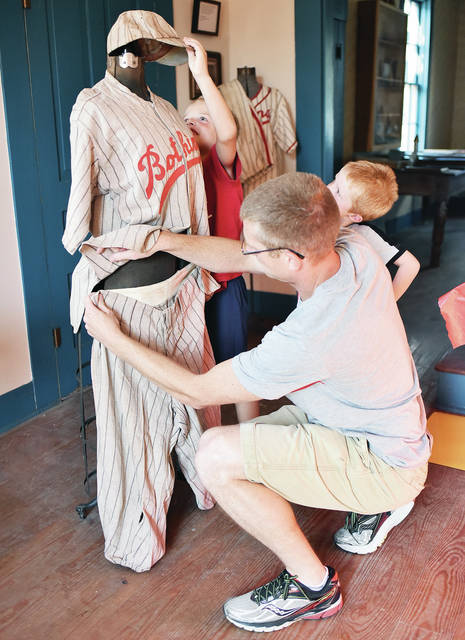Botkins Historical Society President Greg Geis, right, dresses a mannequin in an old Botkins Reds uniform, recently, with his sons, Ian, 6, left, and Olive, 4, all of Botkins. They were preparing the exhibit for the society's annual ice cream social set for Aug. 4.