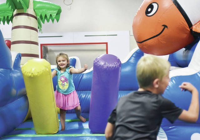 Khloe Righenzi, of Sidney, daughter of Morgan Marvin, play on a bounce house during Y-FEST! presented by Wilson Health Saturday, July 21.