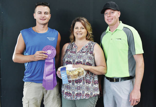 Representing Made in the Shade Tents and Tables Wes Langenkamp, left, and representing Billing Insurance Matt Echols, made the winning bid on the best overall muffins of Wendy Langenkamp, all of Sidney, at the Shelby County Fair Sunday, July 22.