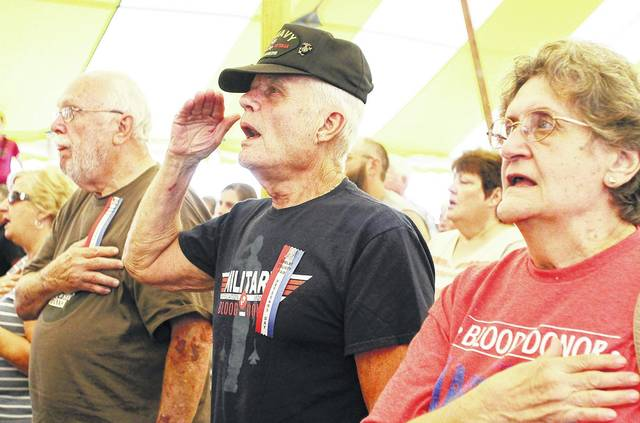 Singing along to the U.S. National Anthem are, left to right, Airforce Vietnam Veteran Leon Stockman, of Fort Loramie, U.S. Marine and Navy Veteran Bill Tady and Theresa Tady, both of Russia. The three were attending last year's Shelby County Fair Veterans Program Monday, July 24, 2017. Tady served 24 years in the U.S. military.