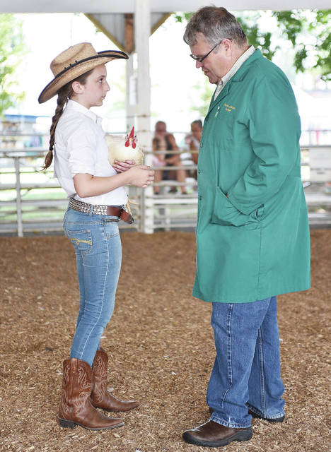 Liliana Phillips, left, 12, of Sidney, daughter of Sonya and Keith Phillips, talks with fair judge David Adkins, of Lucasville, during poultry showmanship at the fair Wednesday, July 25.
