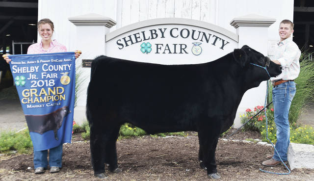 Riley Huelskamp, right, 17, of Anna, son of Chad and Tonya Huelskamp, member of Anna Livestock 4-H Club, with his grand champion market steer at the fair. Holding the banner is his sister Macey Huelskamp, 18.