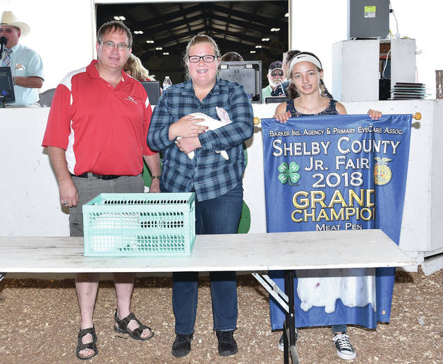 Katelynn Garber, 17, of Sidney, daughter of Eric and Michelle Garber, a member of Starting Farmers, sells her grand champion meat pen of rabbits at the fair Saturday, July 28.