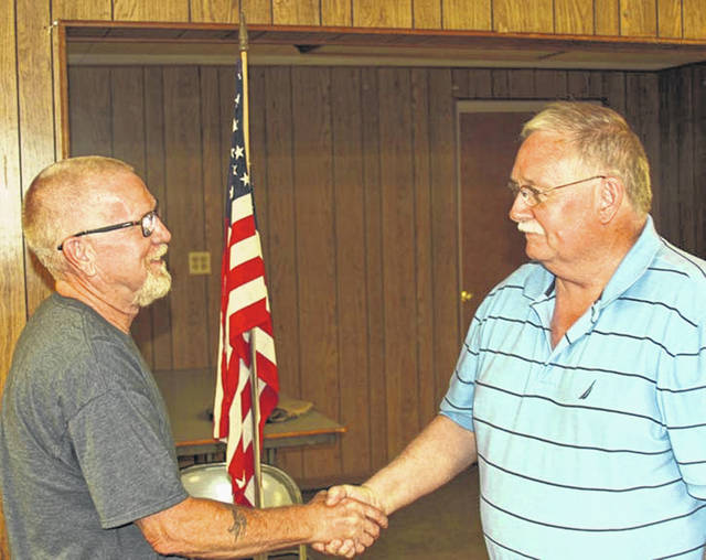 Tim Smith, left, gets a handshake for Port Jefferson Mayor Steve Butterfield after Smith was sworn in as a Port Jefferson Council member, Monday, July 2.