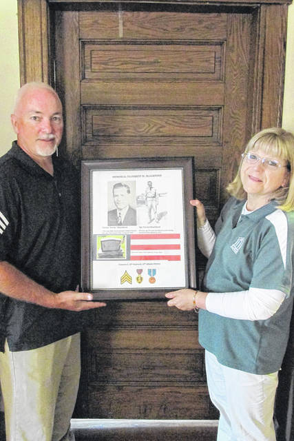 Jamie Whitman, left, an American history and government teacher at Sidney High School, presents a memorial collage about U.S. Army Sgt. Forest Blackford to Tilda Phlipot, director of the Shelby County Historical Society, at the Ross Historical Center in Sidney, recently. Blackford, an Anna native, was killed in action in the Korean War.