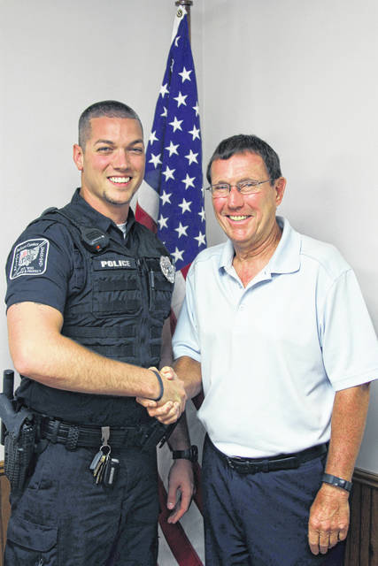Officer Zac Smith, left, receives a congratulatory handshake from Jackson Center Mayor Scott Klopfenstein to acknowledge his appointment as a full-time police officer for the village of Jackson Center. Smith passed the probationary period of six months with flying colors and was praised for his level of service to the community.