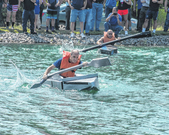 Dave Powers, left, and Dave Welker paddle their cardboard boats during the Emerson Field Days. They will be competing in the Sidney-Shelby County Y-FEST presented by Wilson Health Saturday.