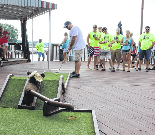 Brandon Mullins, a member of the Putter Nutters team, makes a hole in one in the Lake Improvement Association's Bar Stool Open at Grand Lake St. Marys.