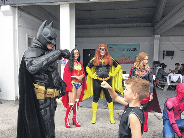 Ryan Kelbel, left, as Batman, fist bumps Logan Breitigam, of Waynesfield, as other superheroes look on during the Auglaize County Fair in Wapakoneta, Tuesday, July 31.