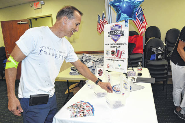 Allan Egbert, of Sidney, drops his ballot into the Police team box after donating blood during the Heroes Behind the Badge Blood Drive in Sidney recently.
