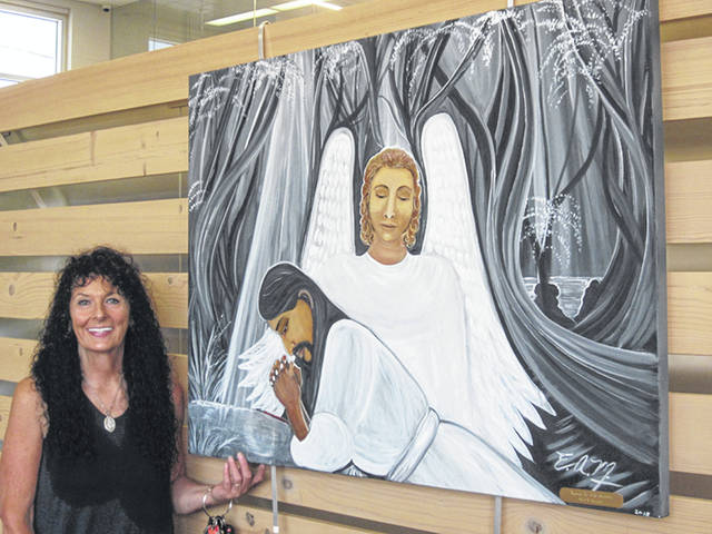 Elizabeth Martinez, of Sidney, with one of her religious-themed paintings, which are on display in the gallery of Amos Memorial Public Library in Sidney through August.