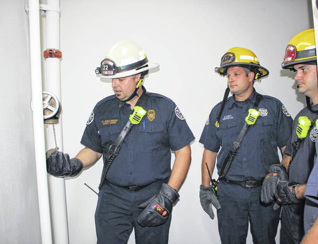 Sidney Fire Department Assistant Chief Chad Hollinger, right, shows Firefighter Brian Lundy the control box for the Canal Place apartments during a fire training exercise Wednesday.