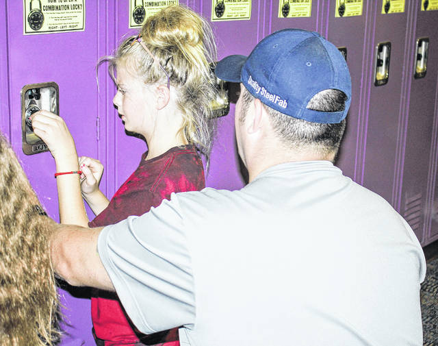 Dustin Morris helps his daughter, Sherri, as she tries to open her locker at the Sidney Middle School open house recently. Sherri is a fifth-grader at the school.