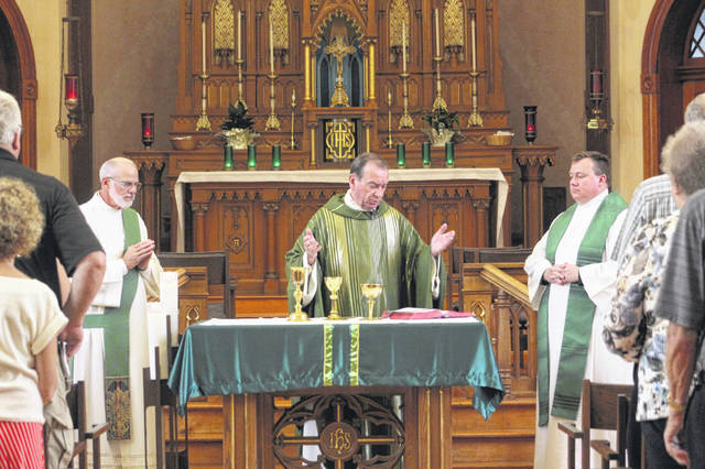 Deacon Clif Perryman, left to right, Archbishop Dennis Schnurr and the Rev. Jeffrey Kirch celebrate a Mass of Thanksgiving for the donors who help make the ministry of the Maria Stein Shrine possible.