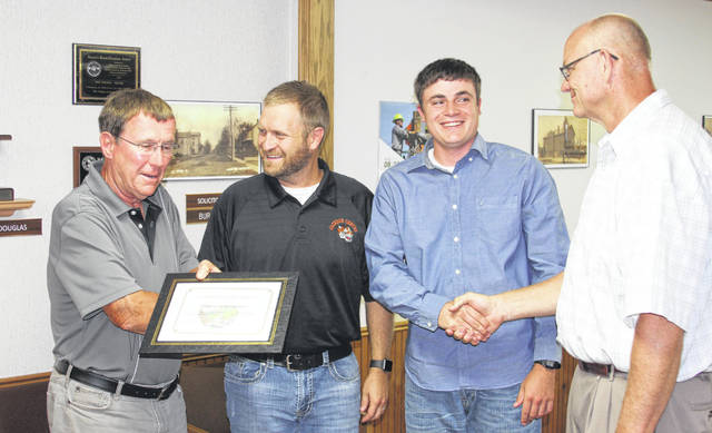Jackson Center Mayor Scott Klopfenstein, left, and Village Administrator Bruce Metz, right, congratulate Water Superintendent Braden Lotz and Water Plant Operator Drew Sosby for receiving recognition and a plaque from the Ohio EPA for implementing a Drinking Water Source Protection Plan.