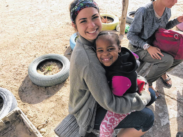 Jessica Witer, left, of Anna, gets a hug from a student in Namibia, where Witer completed a mission trip earlier this month.