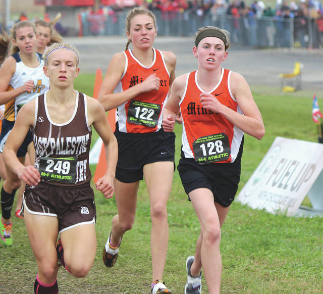 Minster's Emma Watcke, right, and Kaitlynn Albers, center, run in the Division III girls state cross country race on Nov. 5, 2017 at National Trail Raceway in Hebron. Both return for the Wildcats, who won the D-III title for the second consecutive season.