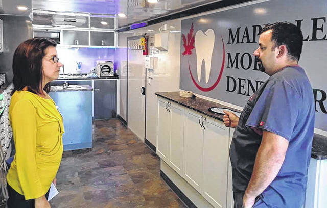 Robin Schmit, left, a social worker at Ohio Living Dorothy Love, talks with Clark Vanmatre, unit manager of the Maple Leaf Mobile Dentistry, which visited the retirement center in Sidney, recently. The state-of-the-art dental clinic on wheels was available to Dorothy Love residents.
