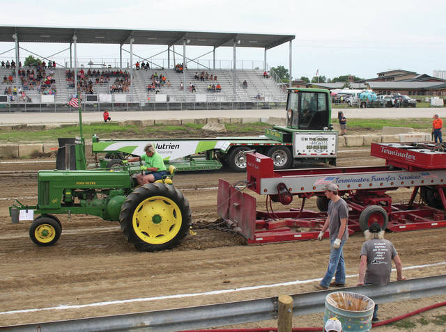 Glee Ann Wills drives a 1952 JD 60 at the fair tractor pull Thursday, July 26.