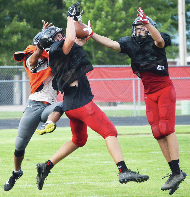 Fort Loramie junior Mark Seger, left, and senior Jake Ratermann, brake up a pass during a scrimmage against Eldia on Friday in Fort Loramie.