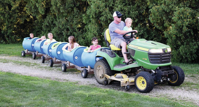 Grant Gehret, of McCartyville, gives the kids a ride around the grounds at the Sacred Heart of Jesus Parish Picnic in McCartyville, Saturday, Aug. 11.