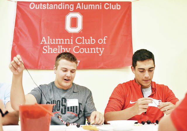 Dylan Smith, left, 18, son of Jayne and Mitch Smith, and Allen Tangeman, 18, both of Sidney, son of Jerry and Daniela Tangeman, make buckeye necklaces during a going away party for local Ohio State University freshmen held by the Ohio State Alumni Club of Shelby County Tuesday, Aug. 14. The event was held at the Sidney American Legion. The alumni club helps freshmen make connections at Ohio State University and give the students support. Smith is majoring in pharmaceutical sciences and Tangeman is majoring in biology and neuroscience.