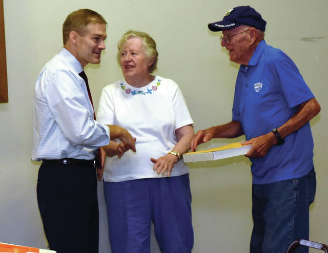 Rep. Jim Jordan, left to right, presents a flag, that was flown over the Capital in Washington, to Phyllis and Dick Carey who won the flag in a drawing at the Shelby County Fair.